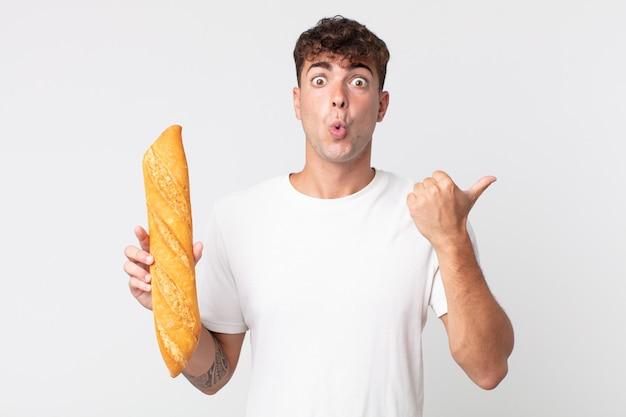 信じられないことに驚いて、パンのバゲットを持っている若いハンサムな男