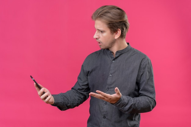 彼の携帯電話の画面を見て若いハンサムな男