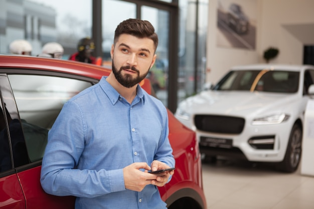 Young handsome man looking away thoughfully while using smart phone at car dealership, copy space