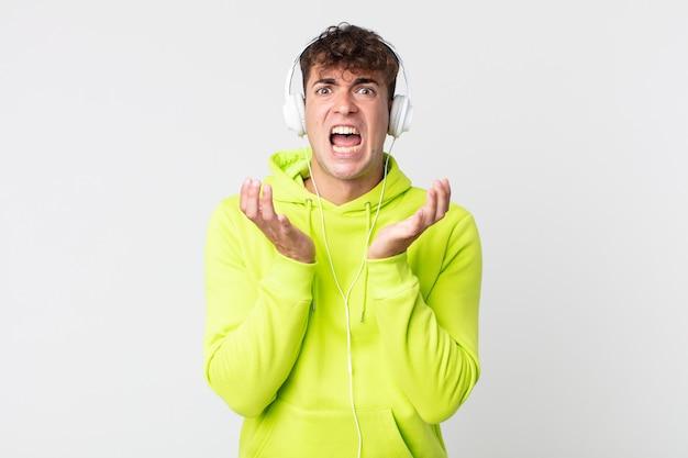 절망적이고, 좌절하고, 스트레스를 받고 헤드폰을 끼고 있는 잘생긴 청년