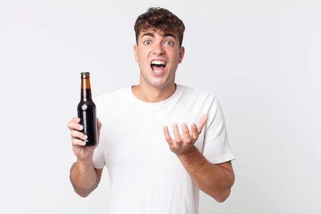 必死になって、欲求不満とストレスを感じ、ビール瓶を持っている若いハンサムな男