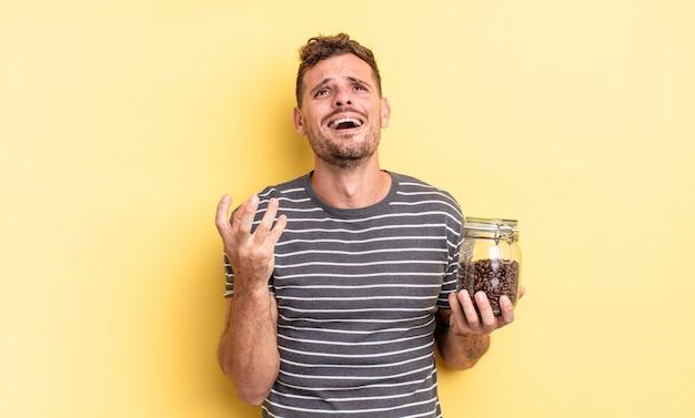 절망적이고, 좌절하고, 스트레스를 받는 커피 콩 개념을 찾고 있는 젊고 잘 생긴 남자