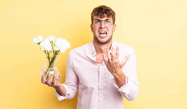Young handsome man looking desperate, frustrated and stressed. flowers concept