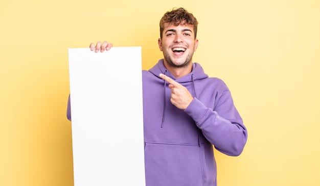 興奮して驚いた若いハンサムな男が横を指しています。コピースペースの概念