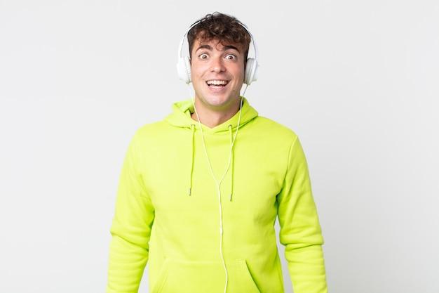幸せそうに見える若いハンサムな男と嬉しい驚きとヘッドフォン