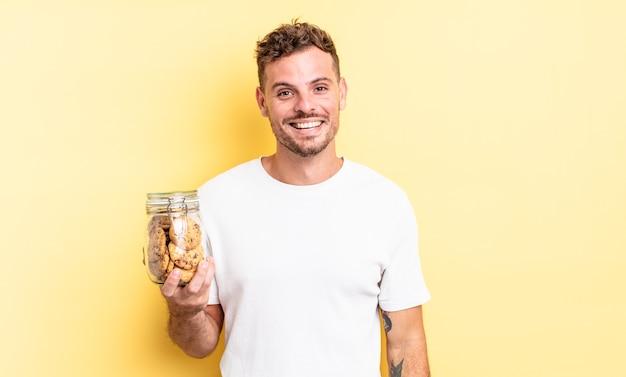 幸せで嬉しい驚きのクッキーボトルのコンセプトを探している若いハンサムな男