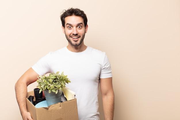 Молодой красивый мужчина выглядит счастливым и приятно удивленным, взволнованным, с очарованным и шокированным выражением лица