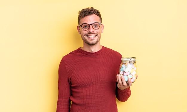 幸せそうに見える若いハンサムな男と嬉しい驚き。ゼリーキャンディーのコンセプト