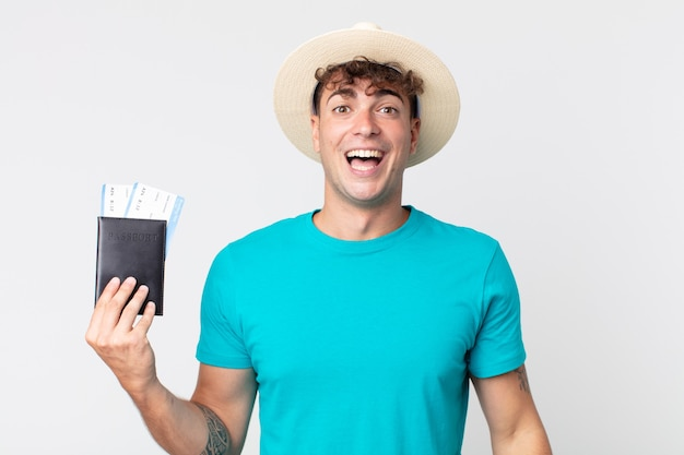 행복 하 고 즐겁게 놀란 찾고 젊은 잘생긴 남자. 여권을 들고 있는 여행자