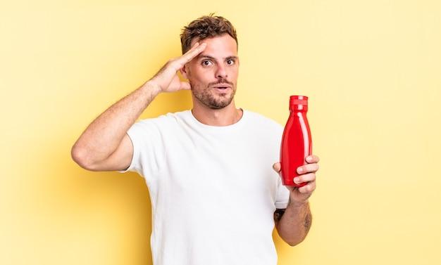 Молодой красивый мужчина выглядит счастливым, удивленным и удивленным. концепция кетчупа