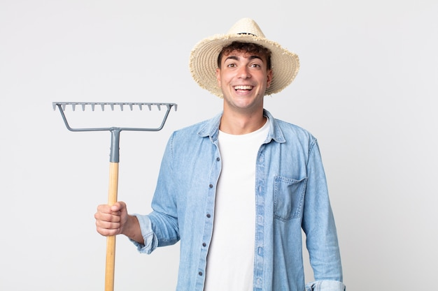 Young handsome man looking happy and pleasantly surprised. farmer concept