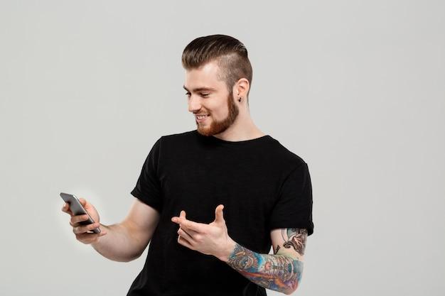 Giovane uomo bello che esamina telefono sopra la parete grigia.