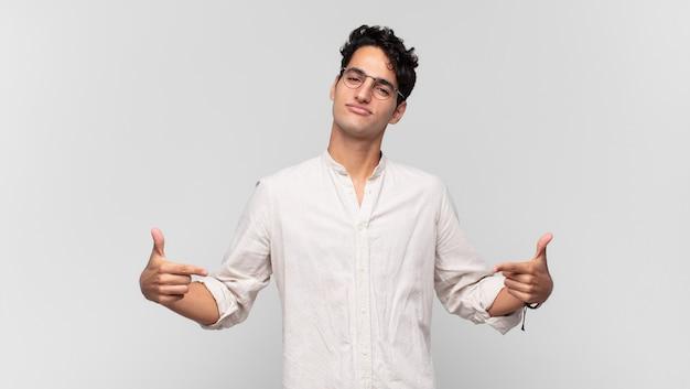 誇らしげに、傲慢で、幸せで、驚き、満足しているように見え、自己を指し、勝者のように感じている若いハンサムな男