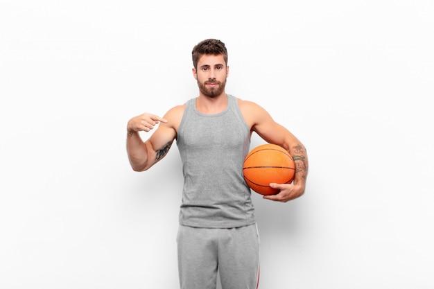 Молодой красавец выглядит гордым, позитивным и непринужденным, указывая на грудь обеими руками с баскетбольным мячом.