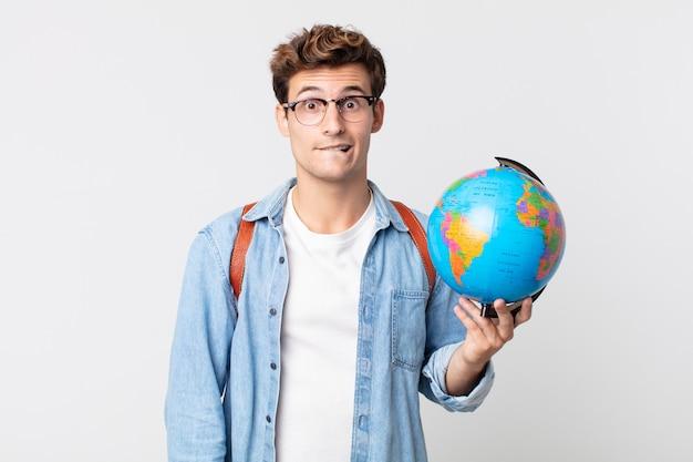 困惑して混乱しているように見える若いハンサムな男。世界の地球地図を持っている学生