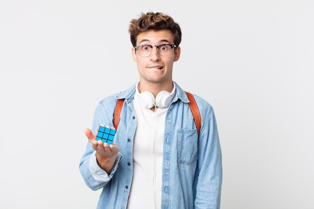 Young handsome man looking puzzled and confused. intelligence game concept