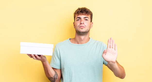 Young handsome man looking serious showing open palm making stop gesture. white box concept
