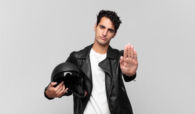 真面目で、厳しく、不機嫌で怒っている若いハンサムな男は、開いた手のひらを停止ジェスチャーを示しています。バイクライダーのコンセプト