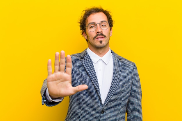 Young handsome man looking serious, stern, displeased and angry showing open palm making stop gesture against orange wall