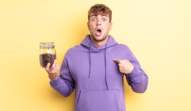 자신을 가리키는 입을 크게 벌리고 놀란 표정을 하고 있는 잘생긴 청년. 커피 콩 개념