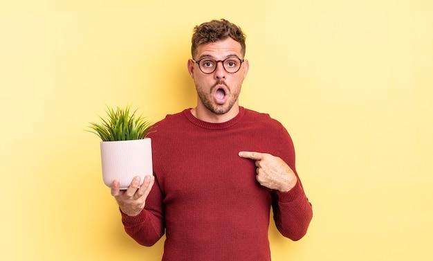 Молодой красивый мужчина выглядит шокированным и удивленным с широко открытым ртом, указывая на себя. концепция декоративного растения