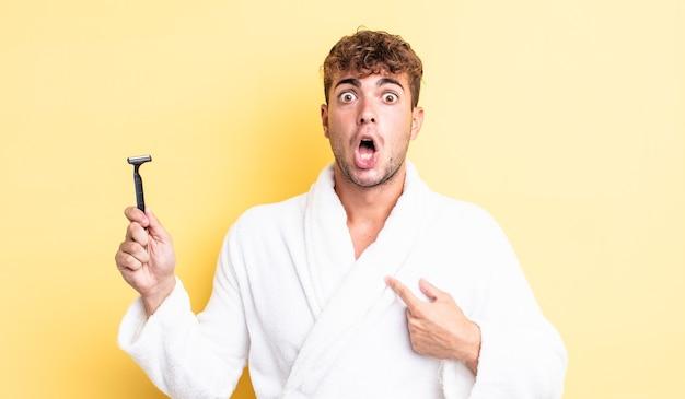 Молодой красивый мужчина выглядит шокированным и удивленным с широко открытым ртом, указывая на себя. концепция бритья