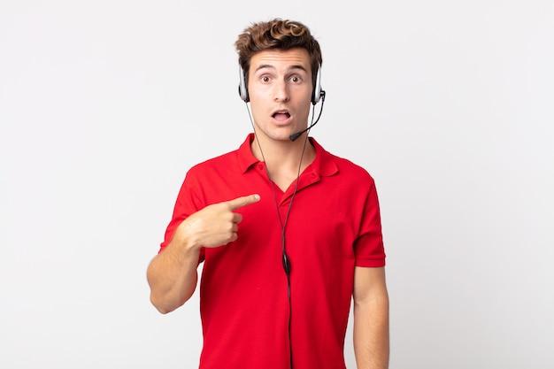 ショックを受けて驚いた若いハンサムな男は、口を大きく開いて、自分を指しています。テレマーケティングの概念