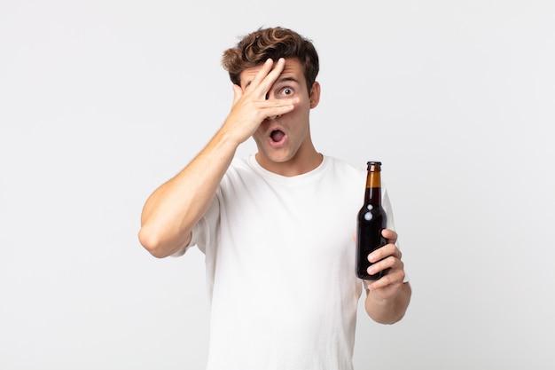 ショックを受けた、怖い、または恐怖を見て、手で顔を覆い、ビール瓶を持っている若いハンサムな男