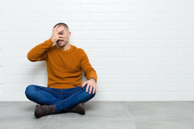 ショックを受けている、怖がっている、または恐怖を探している若いハンサムな男の手で顔を覆っていると床に座っている指の間を覗く