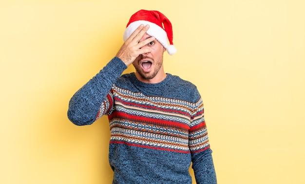 충격, 겁 또는 겁에 질려 보이는 젊은 잘생긴 남자, 손으로 얼굴을 덮고. 크리스마스 컨셉