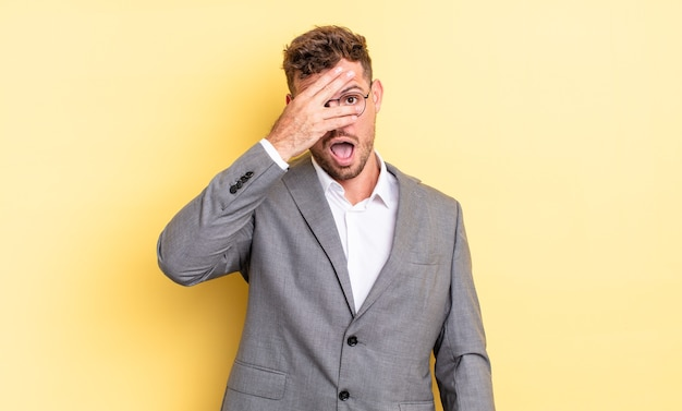 Young handsome man looking shocked, scared or terrified, covering face with hand. business concept