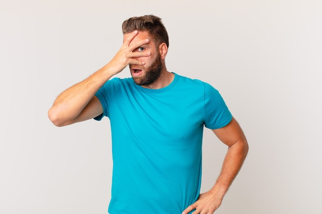 Young handsome man looking shocked, scared or terrified, covering face with hand. fitness concept
