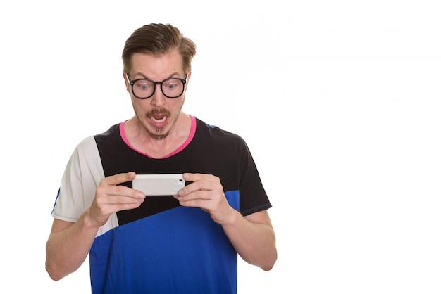 携帯電話を使用している間ショックを探している若いハンサムな男