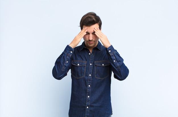 ストレスと欲求不満を探している若いハンサムな男、頭痛で圧力の下で働いて、青い壁に対する問題で悩んで