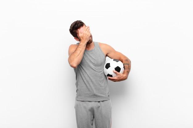 サッカーボールを持っている手で顔を覆っている、ストレス、恥ずかしさ、または動揺、頭痛で探している若いハンサムな男