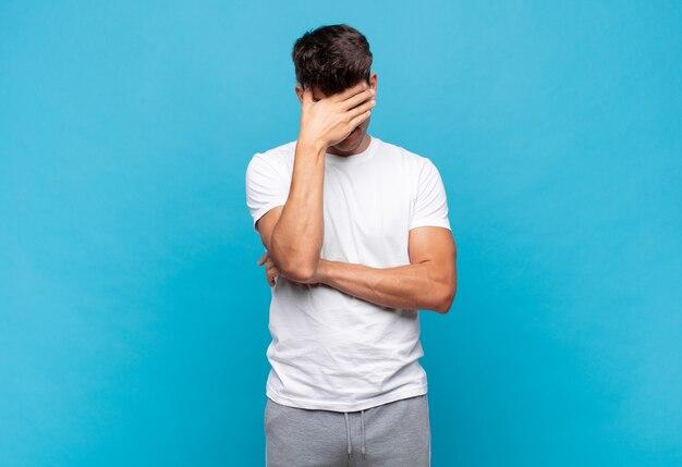 ストレス、恥ずかしがり屋、または動揺して、頭痛で、手で顔を覆っている若いハンサムな男