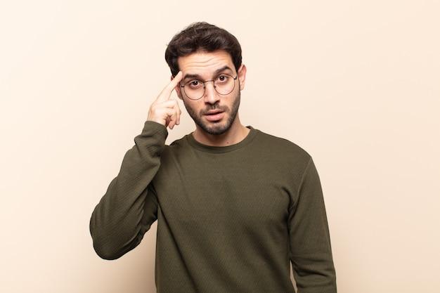 Молодой красивый мужчина выглядит удивленным, с открытым ртом, шокированным, осознающим новую мысль, идею или концепцию