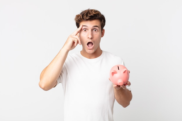 Young handsome man looking surprised, realizing a new thought, idea or concept and holding a piggy bank