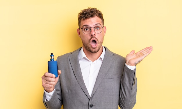 Young handsome man looking surprised and shocked, with jaw dropped holding an object. vaporizer concept