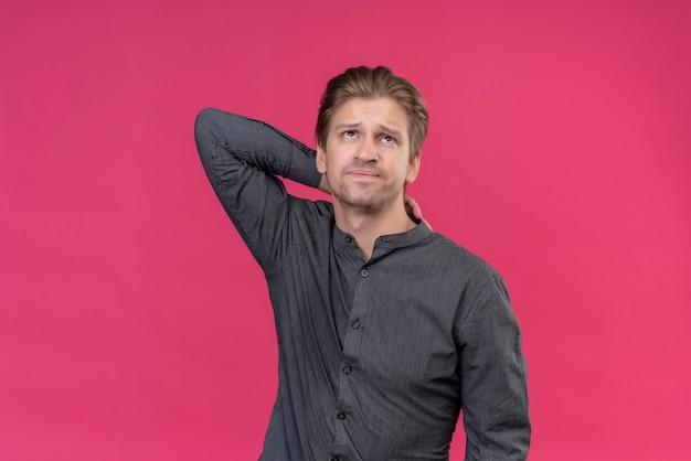 ピンクの壁の上に立って首に触れて疲れて退屈そうに見えて若いハンサムな男