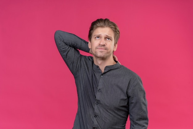 Young handsome man looking tired and bored touching his neck standing over pink wall