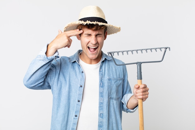Young handsome man looking unhappy and stressed, suicide gesture making gun sign. farmer concept