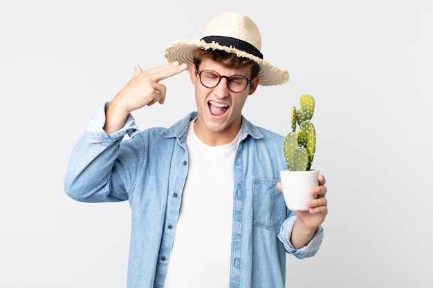Young handsome man looking unhappy and stressed, suicide gesture making gun sign. farmer holding a decorative cactus