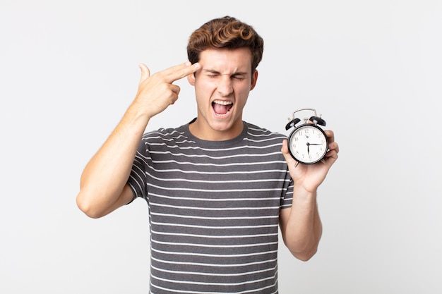 Young handsome man looking unhappy and stressed, suicide gesture making gun sign and holding an alarm clock