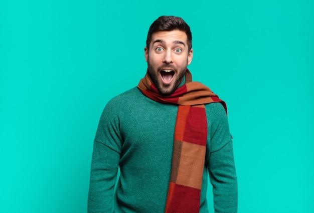 매우 충격을 받거나 놀란 것처럼 보이는 젊은 잘생긴 남자가 입을 벌리고 와우라고 말합니다. 추위와 겨울 개념