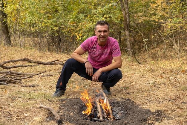 若いハンサムな男は、秋の森の屋外でキャンプファイヤーを作ります。森の中の焚き火