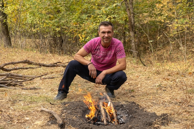 Young handsome man makes a campfire outdoors in the autumn forest. bonfire in the woods