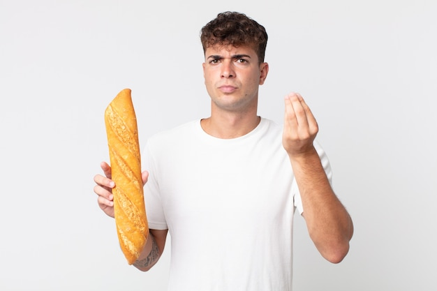 Young handsome man making capice or money gesture, telling you to pay and holding a bread baguette