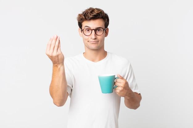 젊고 잘생긴 남자가 돈을 내거나 돈을 지불하라고 말하고 커피 컵을 들고 있다