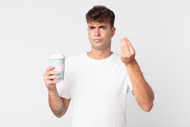 젊고 잘생긴 남자가 테이크 아웃 커피를 들고 돈을 내라고 말하고 돈을 벌거나 몸짓을 한다